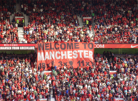 Our Manchester theme continues, and United fans welcome City to their stadium with a not-so-subtle dig.