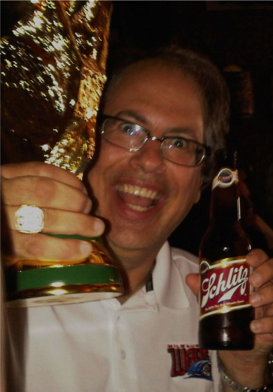 "Peter Wilt celebrating the US win over Algeria with the World Cup Trophy in one hand and the ""Beer That Made Milwaukee Famous"" in the other. Fake World Cup Trophy, real joy."