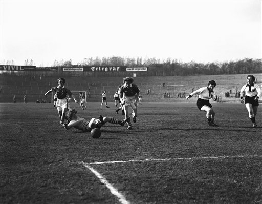 The goalkeeper of a West German ladies soccer team goes down in all-out effort to prevent score but the ball rolls through for a goal, Nov. 3, 1957. Moving in are Mary Bee, left, and Margaret Hilton of British team which won match, 4-0, for the European Ladies Soccer Championship in West Berlin, Germany. (AP Photo)